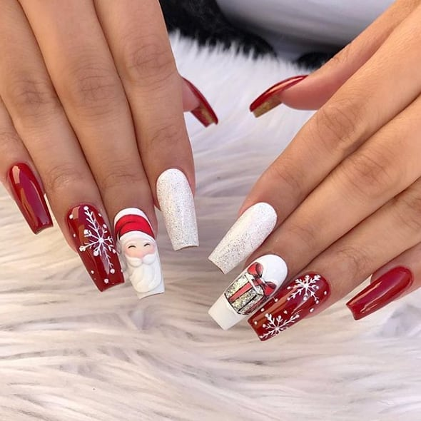 Red and white Christmas nails with snowflakes and Santa Claus nail art - coffin shaped acrylic nails