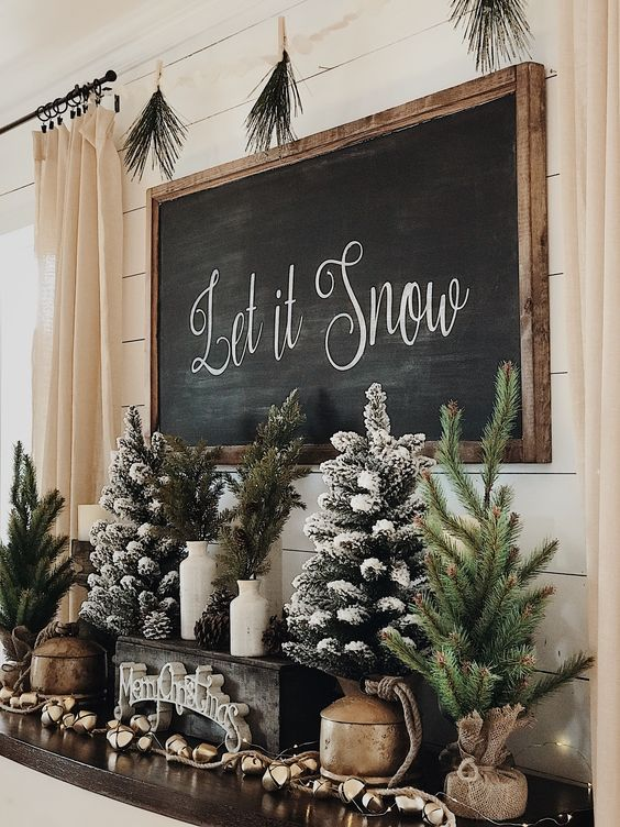 """Rustic Christmas decor with """"Let It Snow"""" black board and mini Christmas trees"""