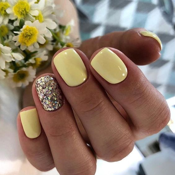 Pale yellow nails with glitter