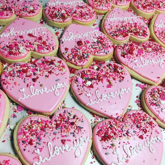Cute valentine's day cookies and pink heart shaped cookies with sprinkles