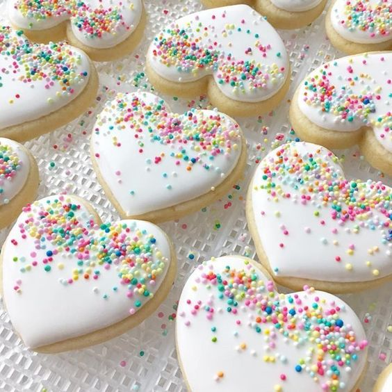 Cute valentine's day cookies and white heart shaped cookies with sprinkles