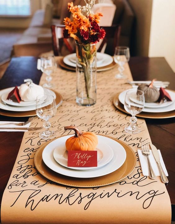 Elegant Thanksgiving table settings with elegant table runner and pumpkins