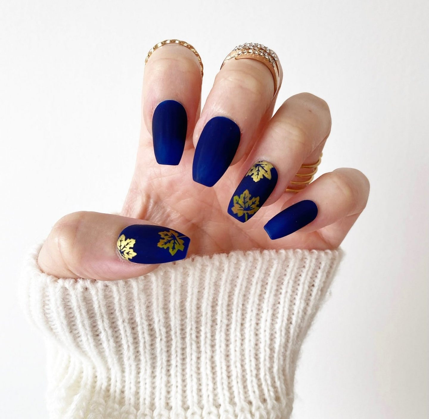 Matte royal blue nails with gold maple leaves
