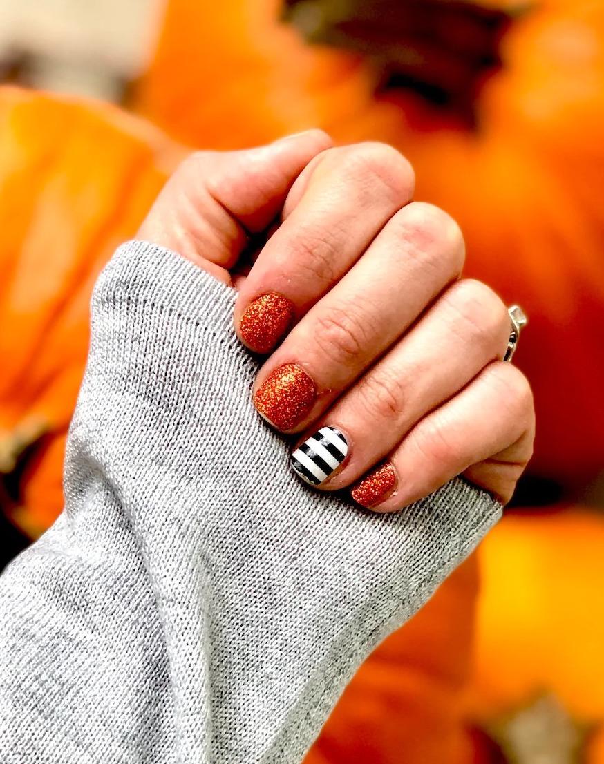 Short burnt orange glitter nails with black and white stripes