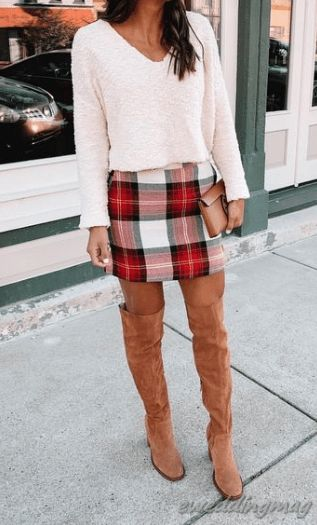 Red tartan skirt and white sweater outfit with tan boots