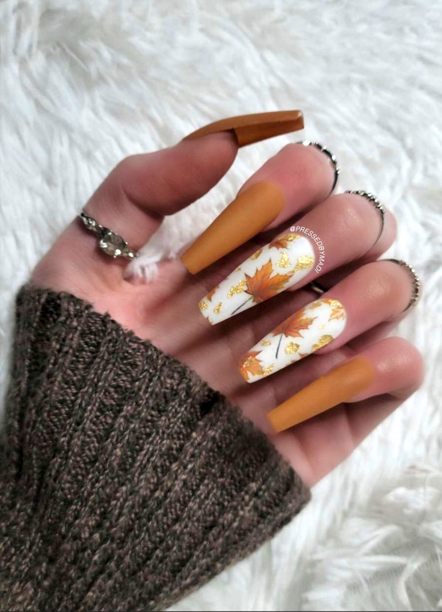Burnt orange Thanksgiving nails with maple leaf nail art