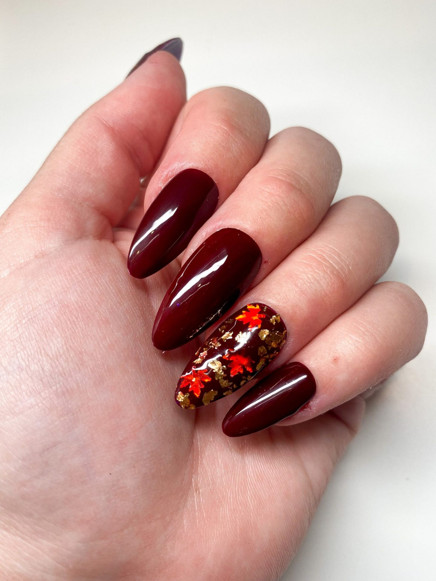 Burgundy Thanksgiving nails with fall foliage