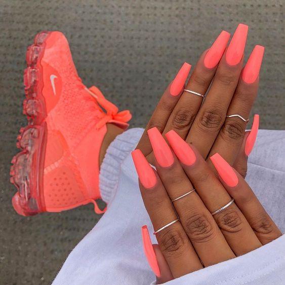 Bright orange summer nails in coffin shape