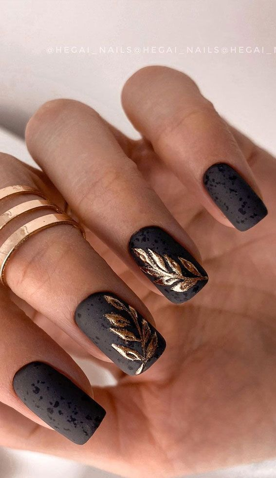 Matte black and gold foil nail art with speckles