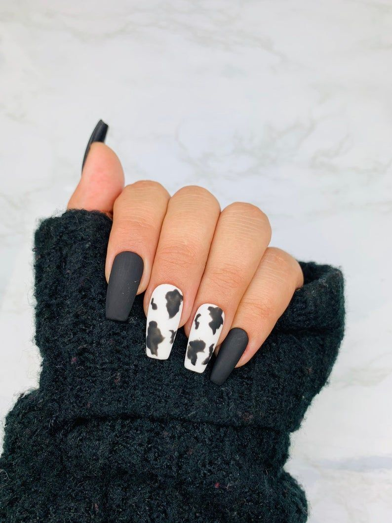 Matte black and white cow print nails