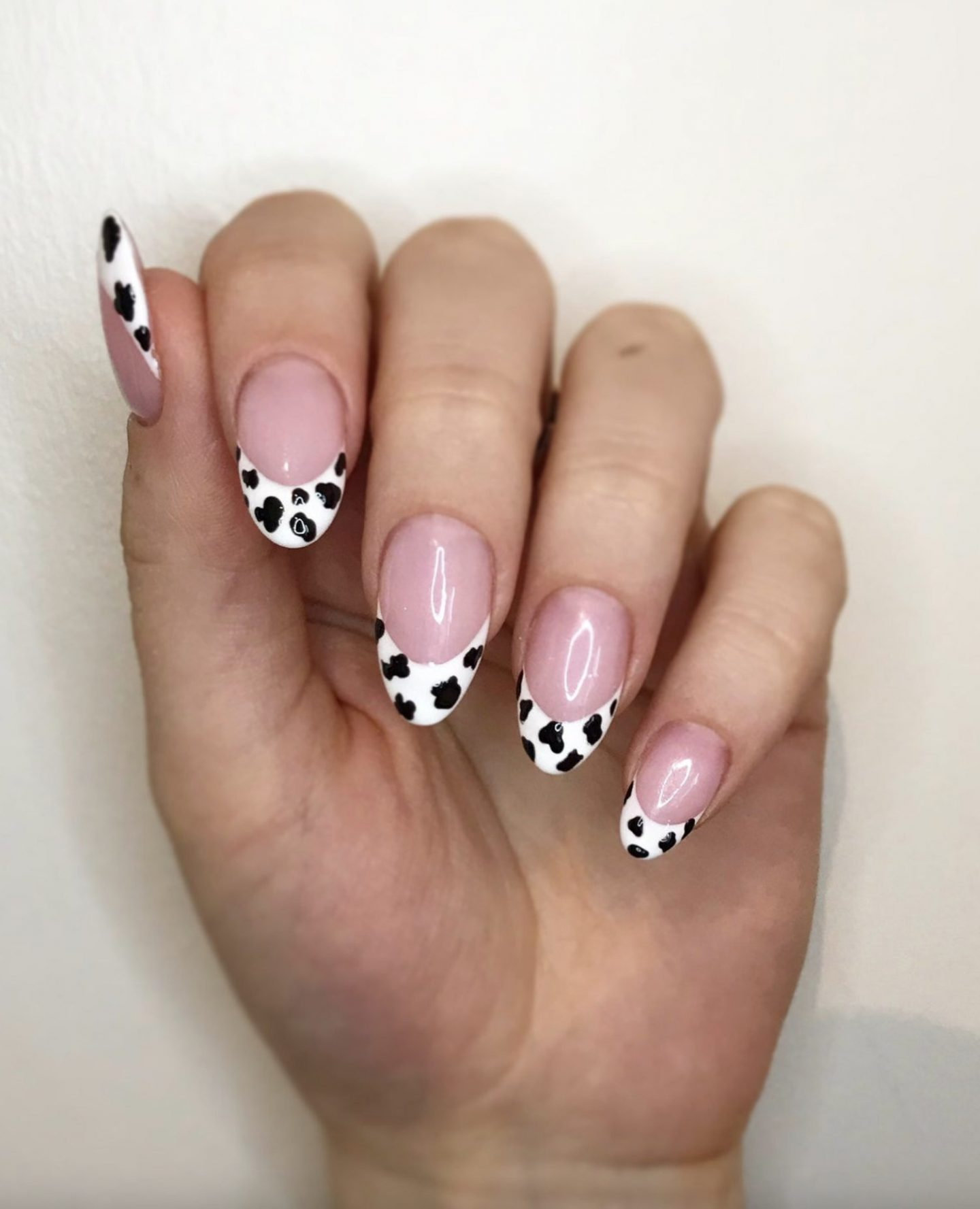 Cow print French tip nails with pink polish