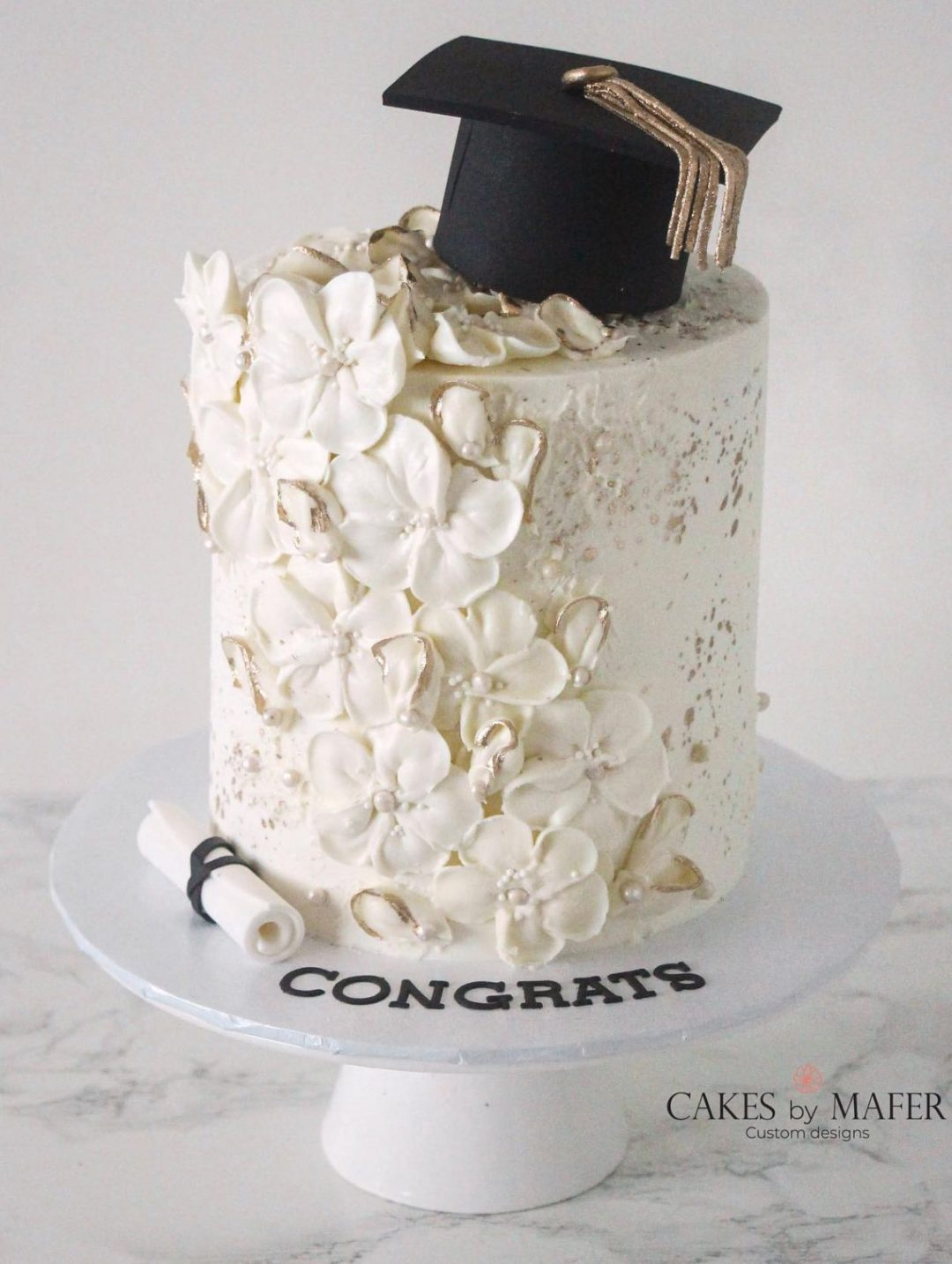 Elegant white graduation cake with flowers
