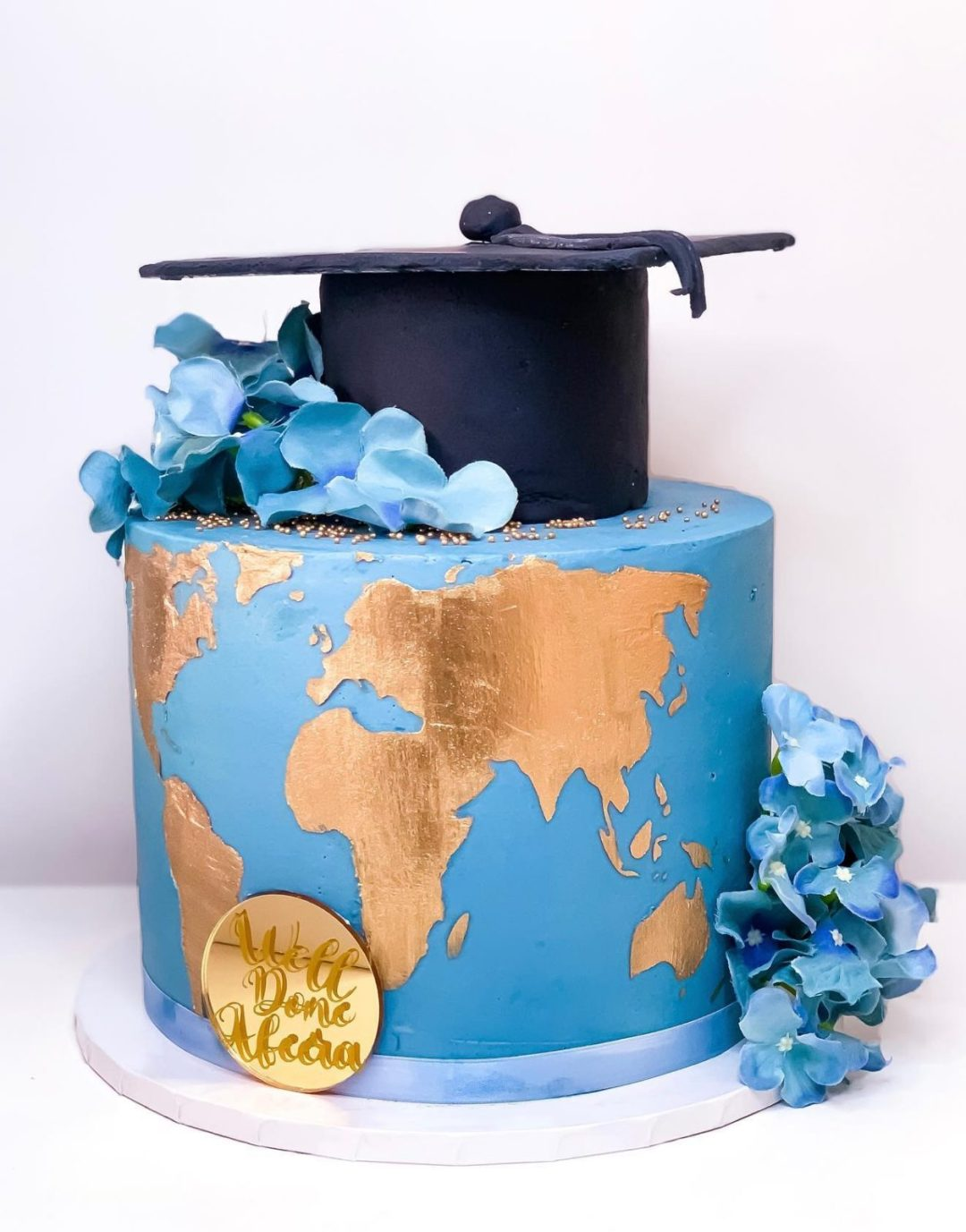 Blue graduation cake with world map for geography grads