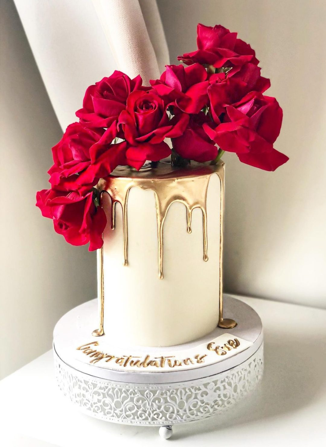 Elegant graduation cake with roses and dripping gold