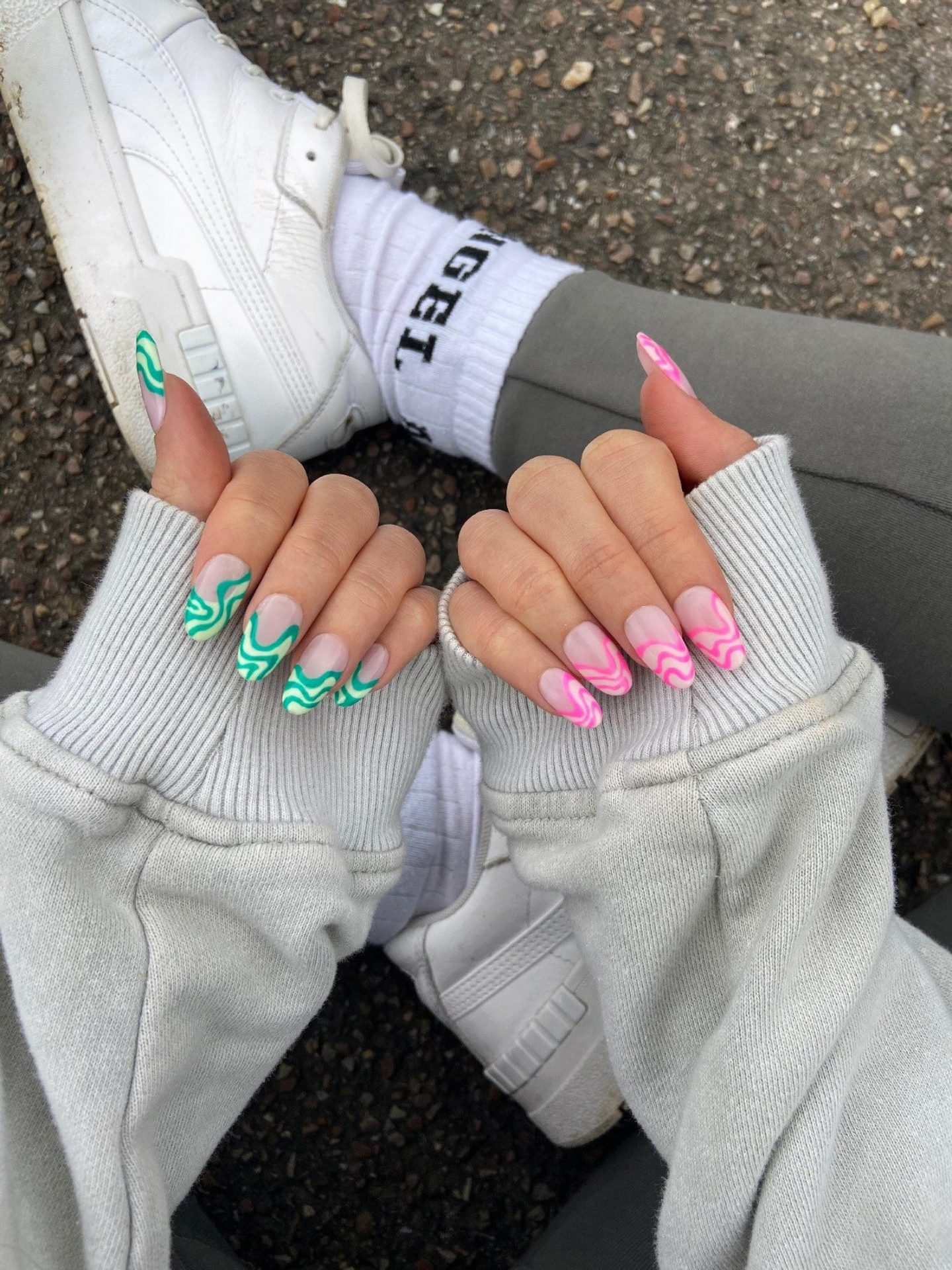 Green and pink French tip nails with swirls