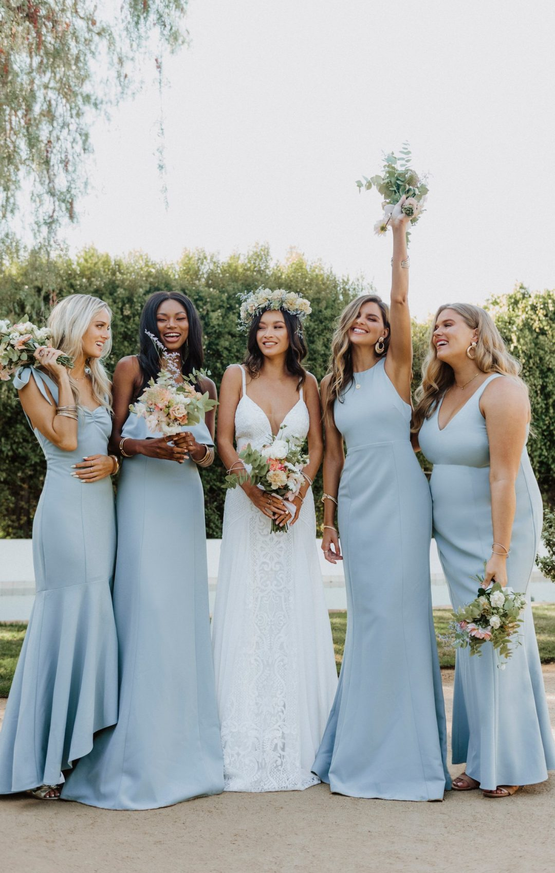 Mismatched dusty blue bridesmaid dresses with mermaid tail