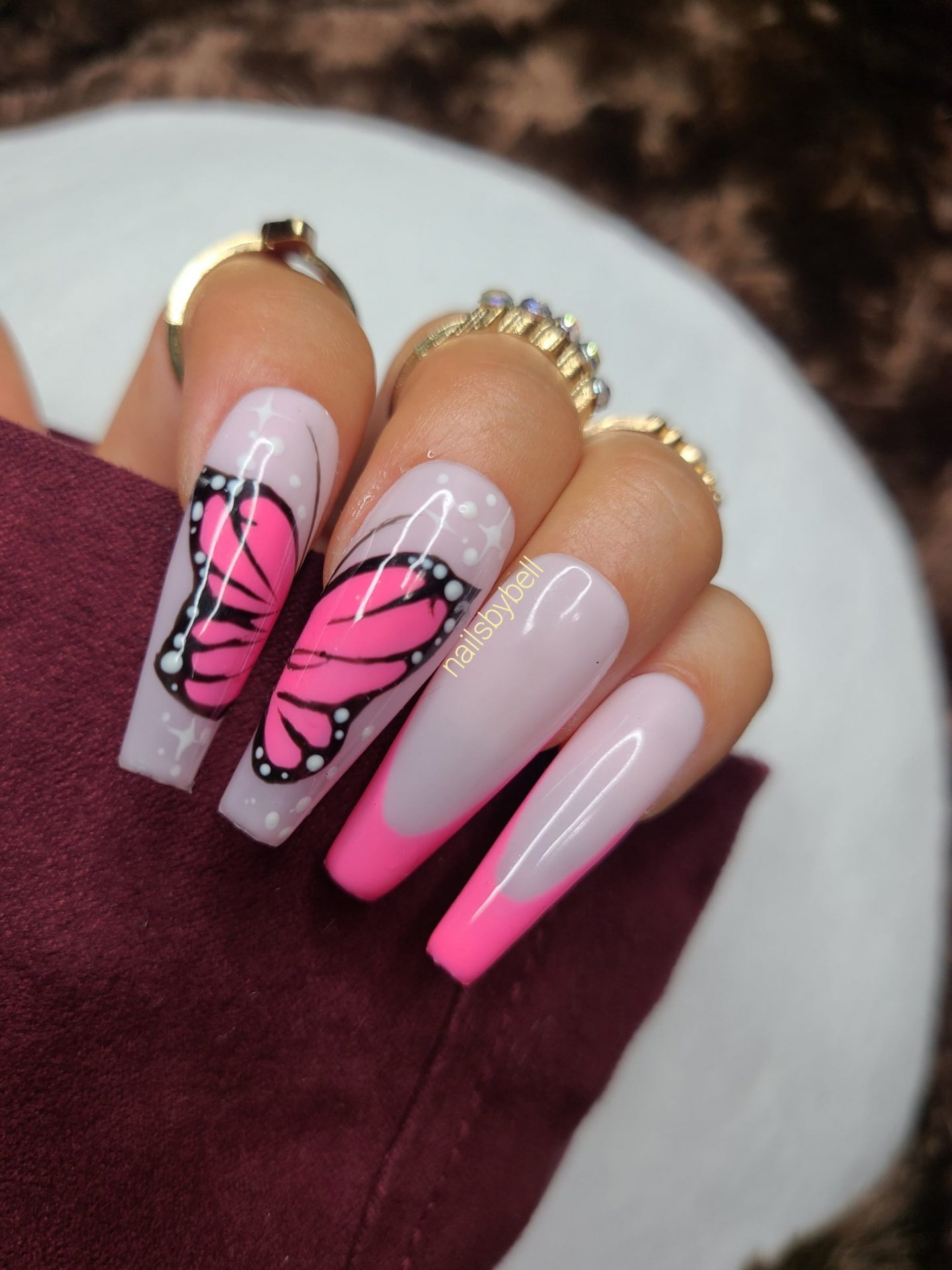 Hot pink French tip nails with butterfly nail art