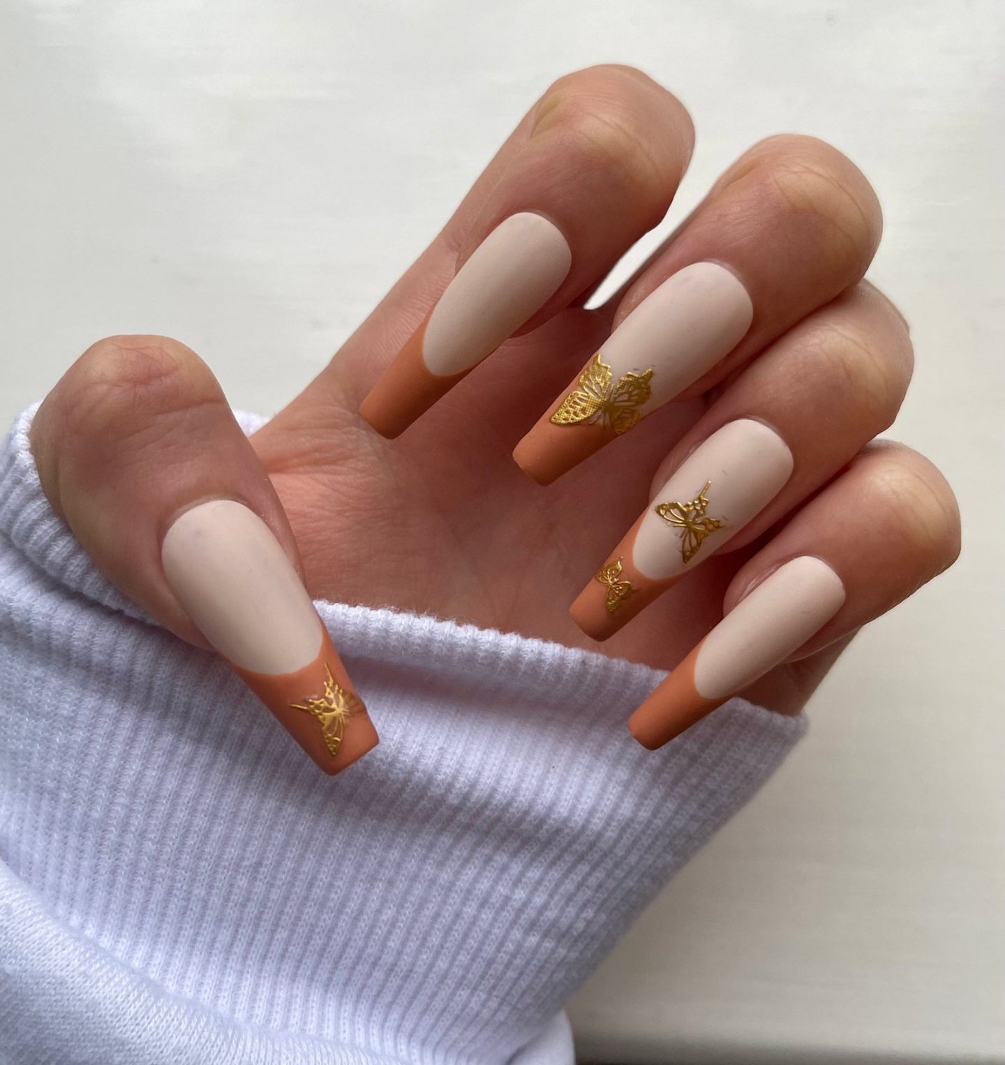 Brown French tip nails with butterfly nail stickers