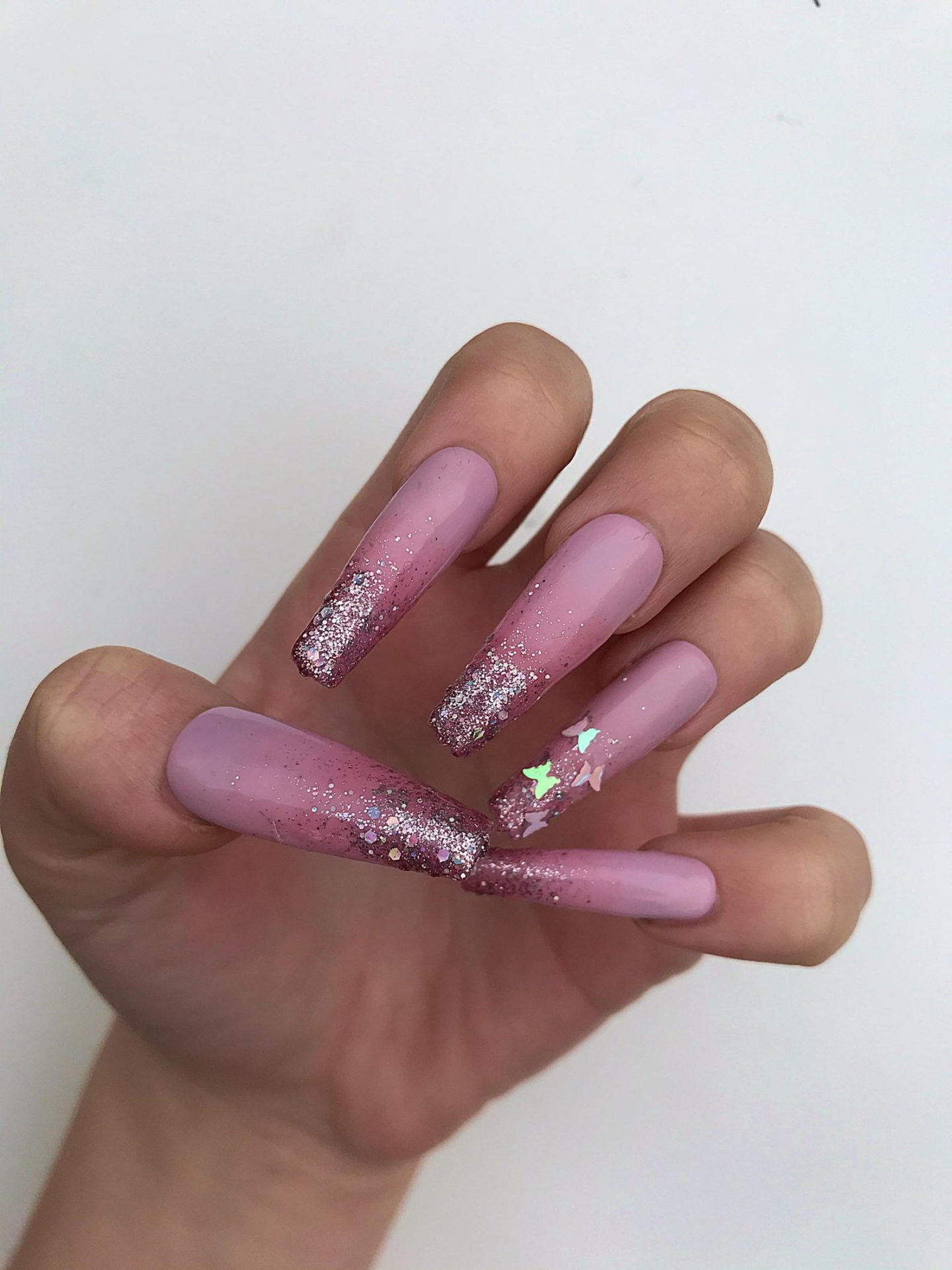 Pink butterfly nails with glitter in acrylic coffin shape