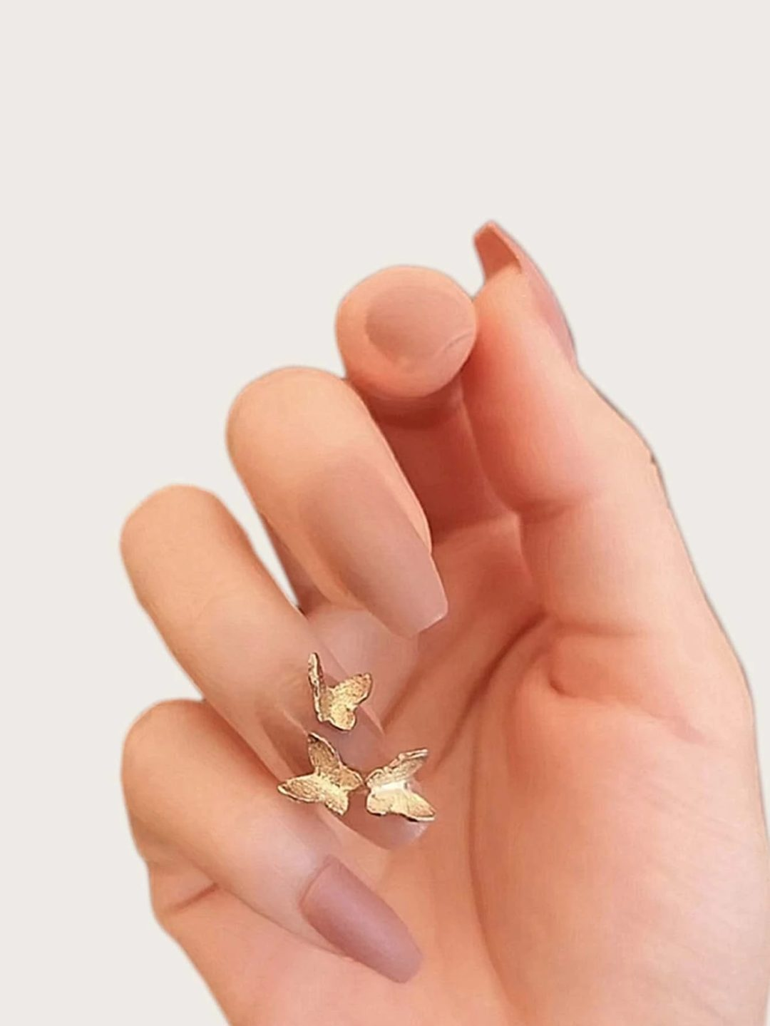 Nude nails with 3D gold butterfly ornaments