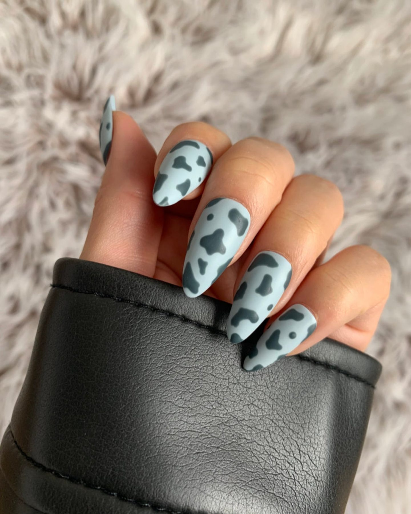 Light blue cow nails in almond shape