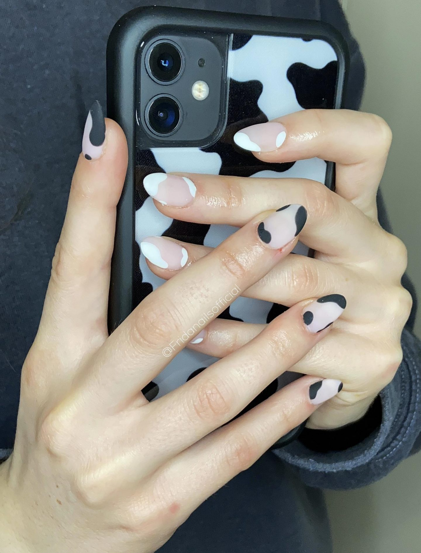Matte black and white cow print nails with negative space