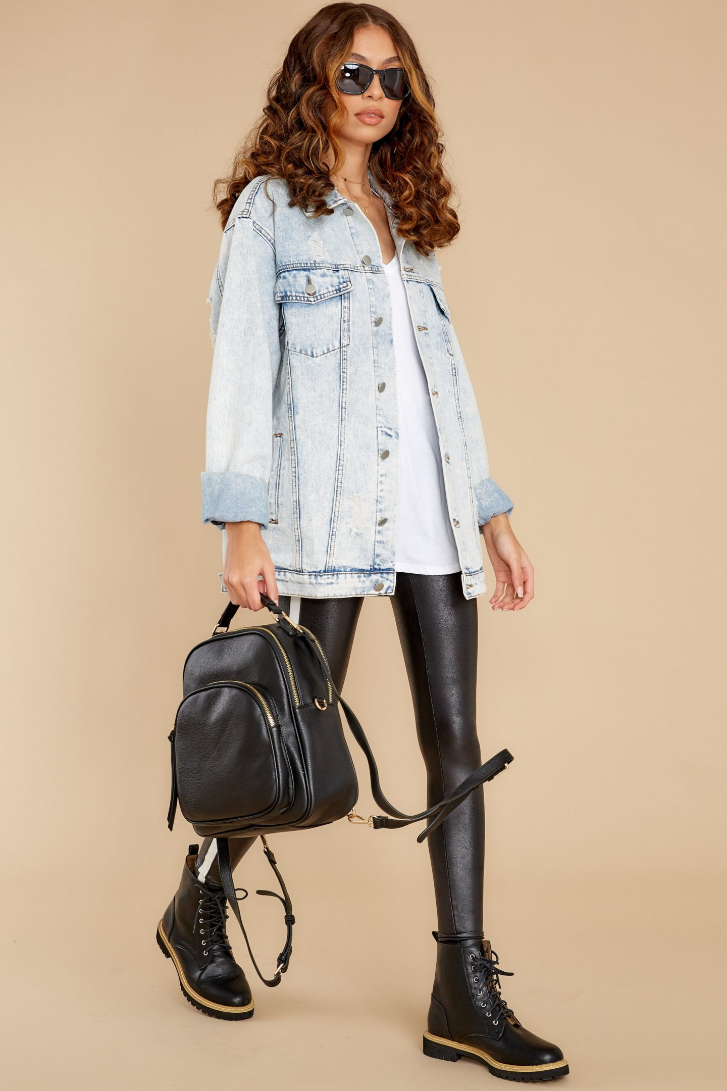 Light denim jacket outfit with combat boots and faux leather leggings