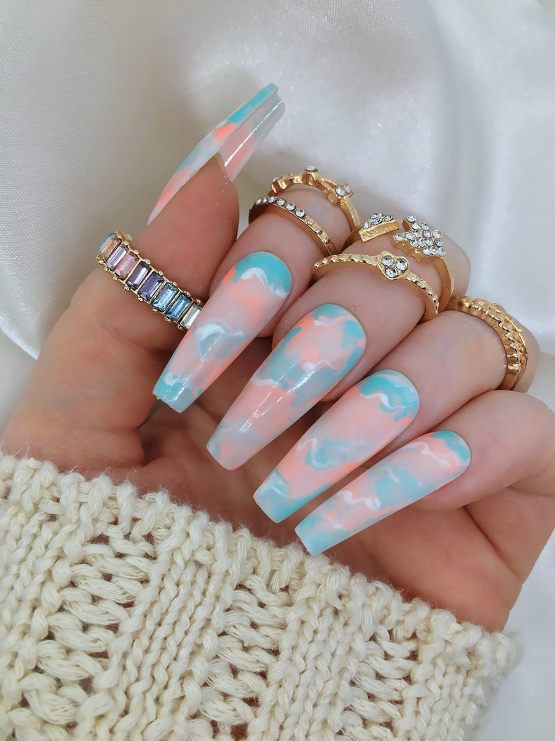 Pastel blue and orange nail designs in acrylic coffin shape