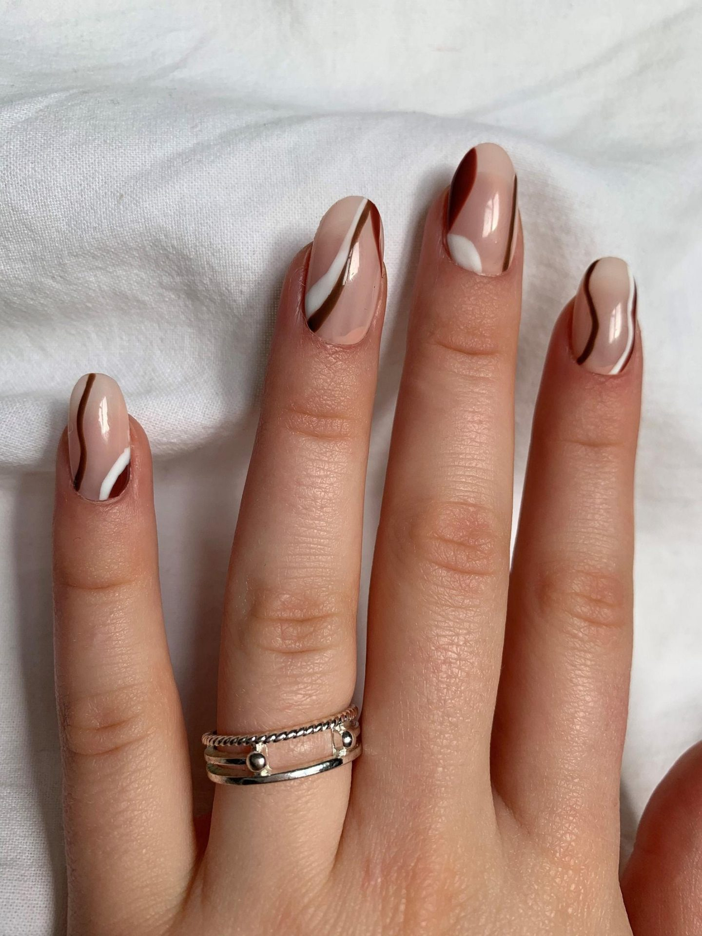 Abstract nails with white and brown swirls and lines
