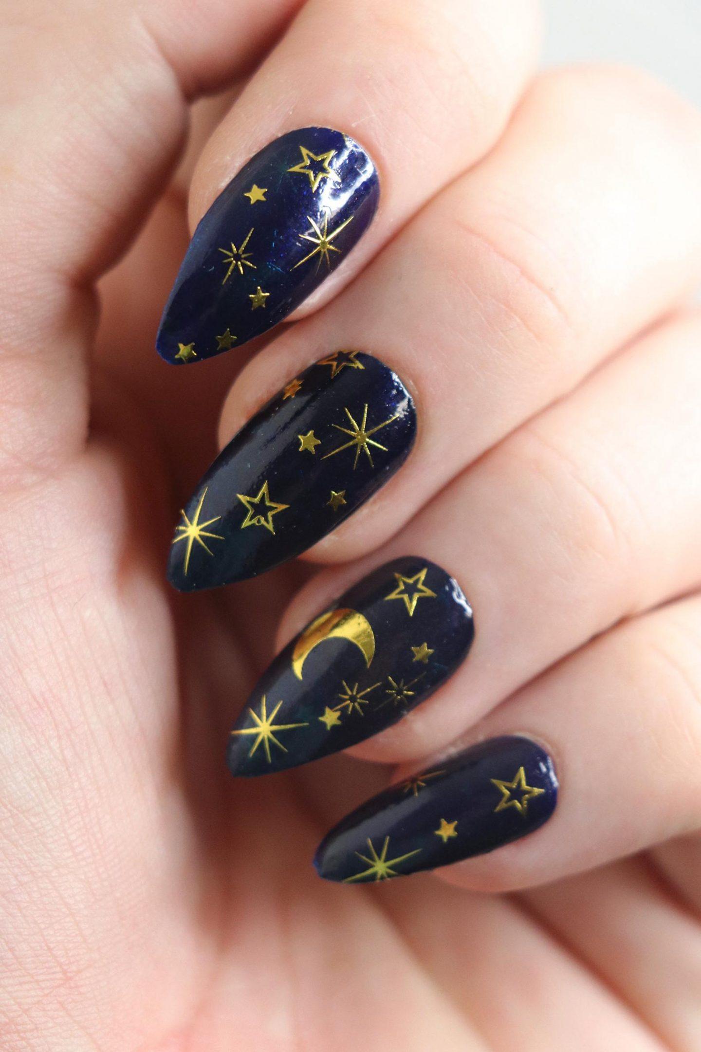 Black nails with gold moon and stars nail art