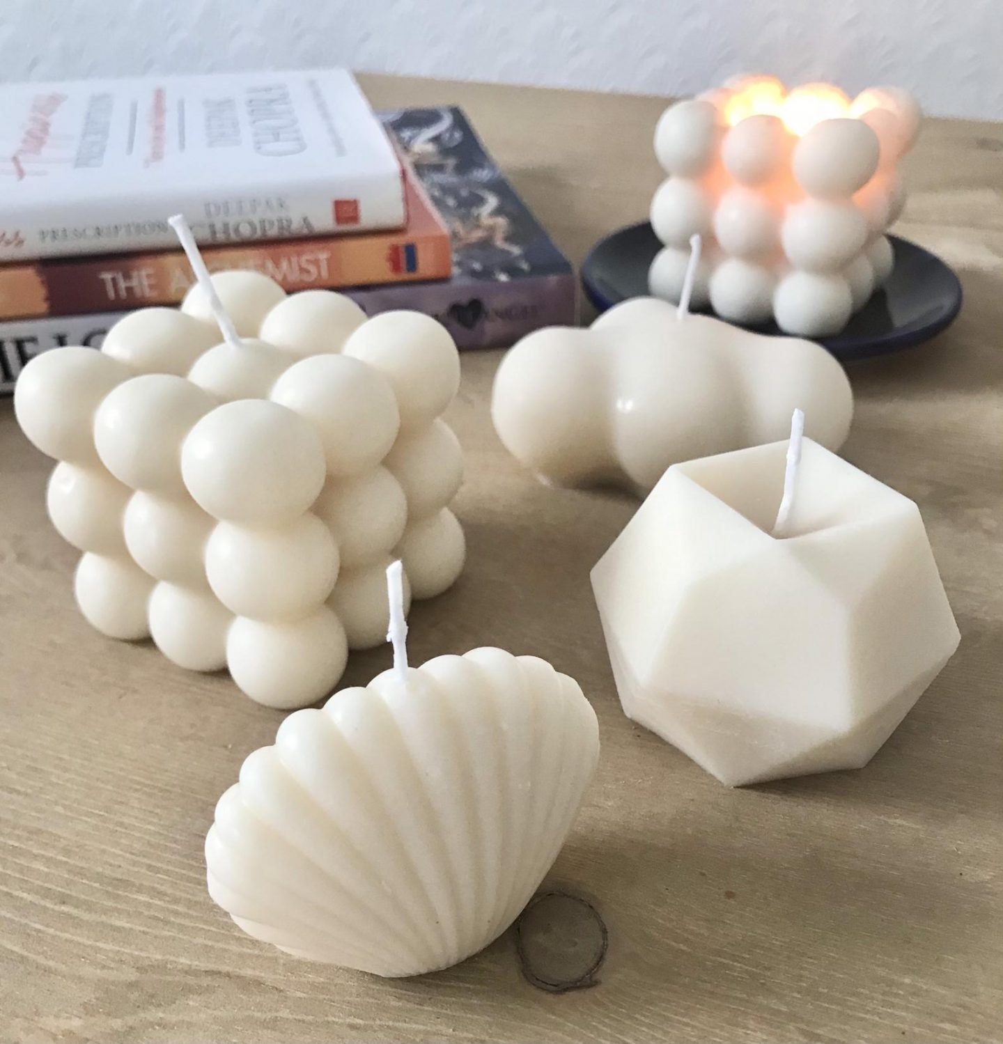 Trendy white sculptural candles in shell, cube, knot and more shapes