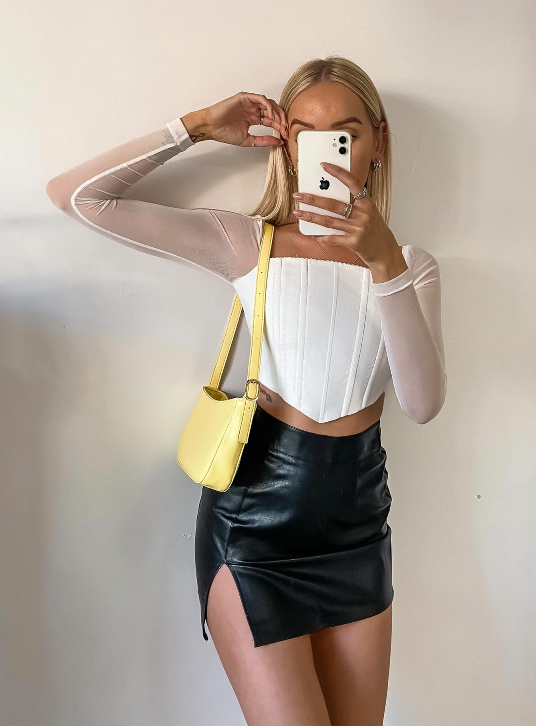 White mesh corset top with black faux leather skirt