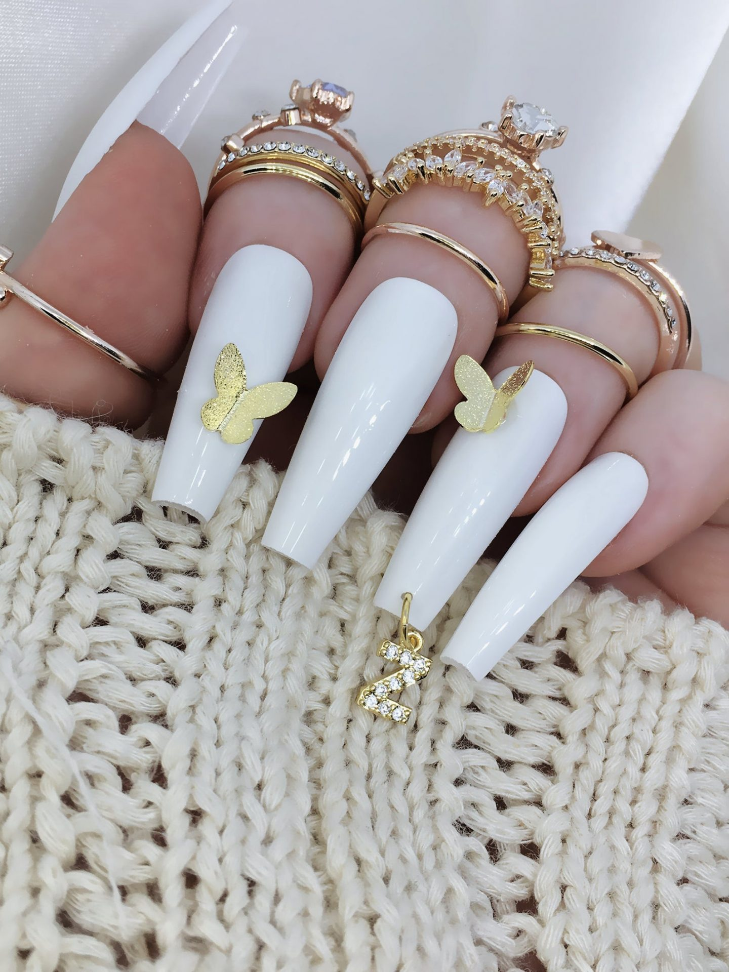 Long white coffin nails with3D gold butterfly nail art