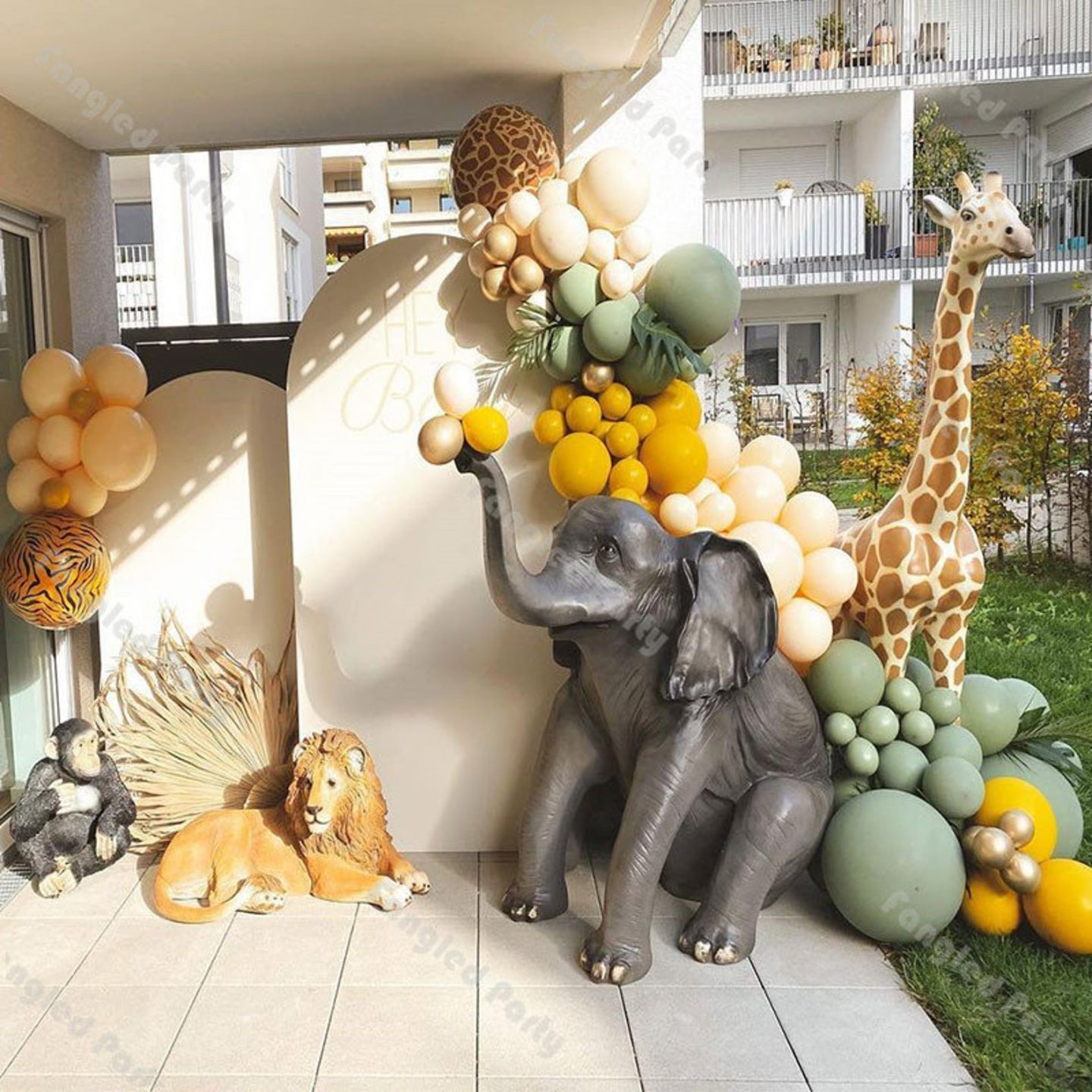 Safari themed birthday party decor with elephant, lion and giraffe and balloons