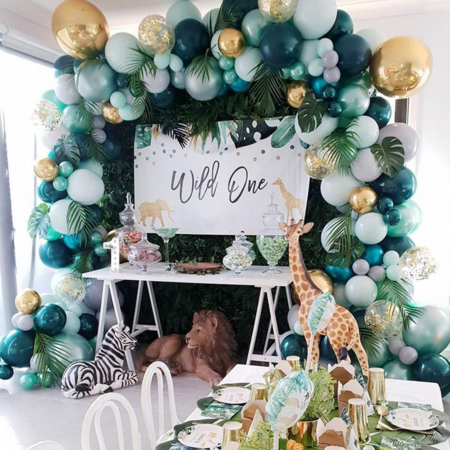 Safari themed birthday party decorations with green balloons