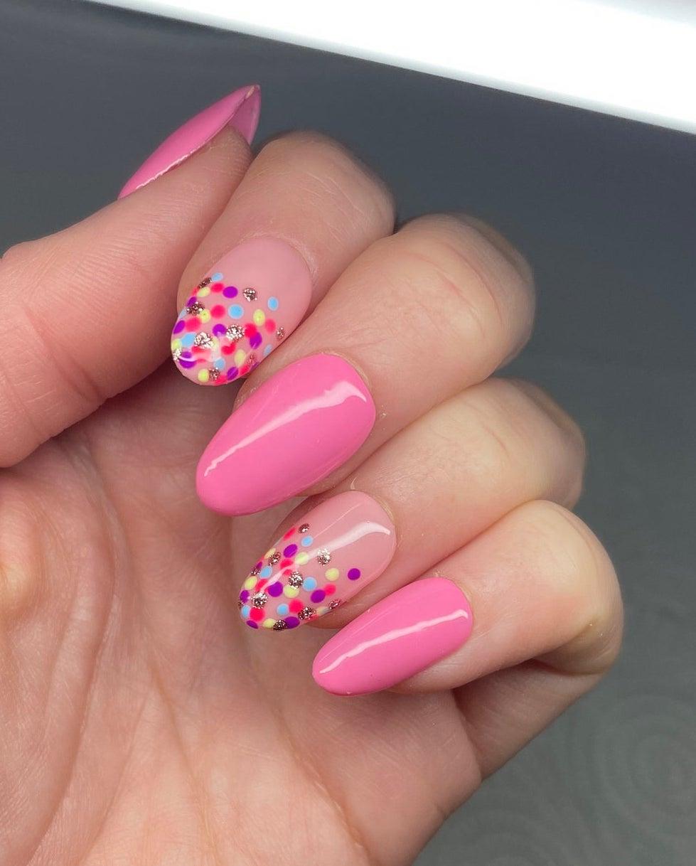 Cute hot pink nails with colorful polka dots