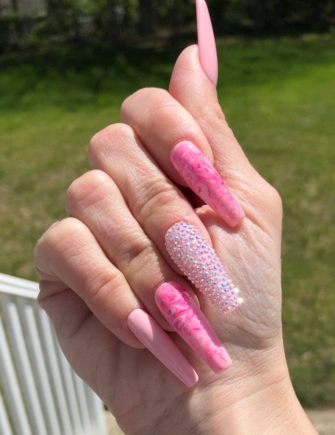 Long bubblegum pink nails with rhinestones