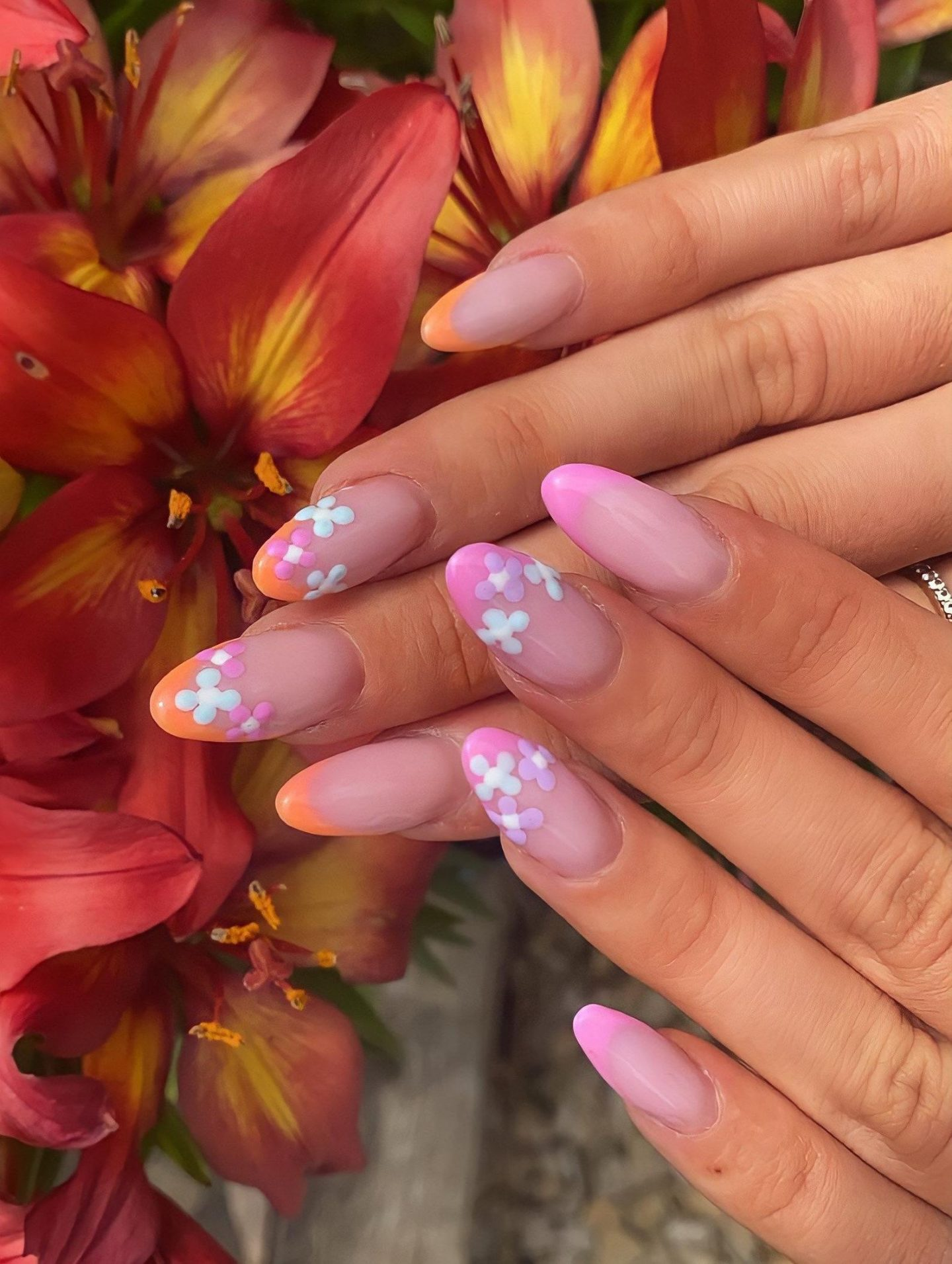 Orange and pink French tip nails with flower nail art
