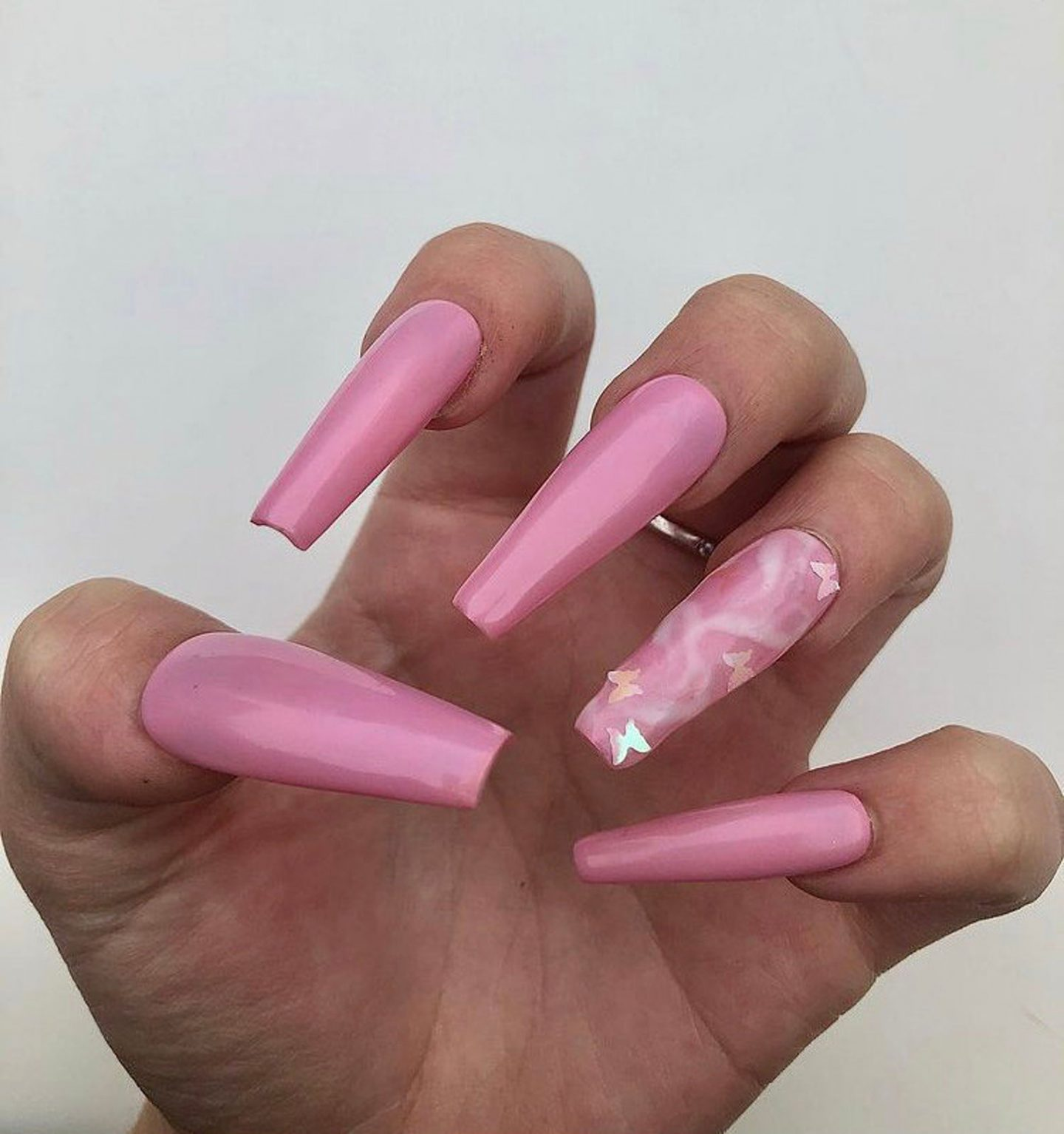 Bubblegum pink acrylic coffin nails with butterfly nail art