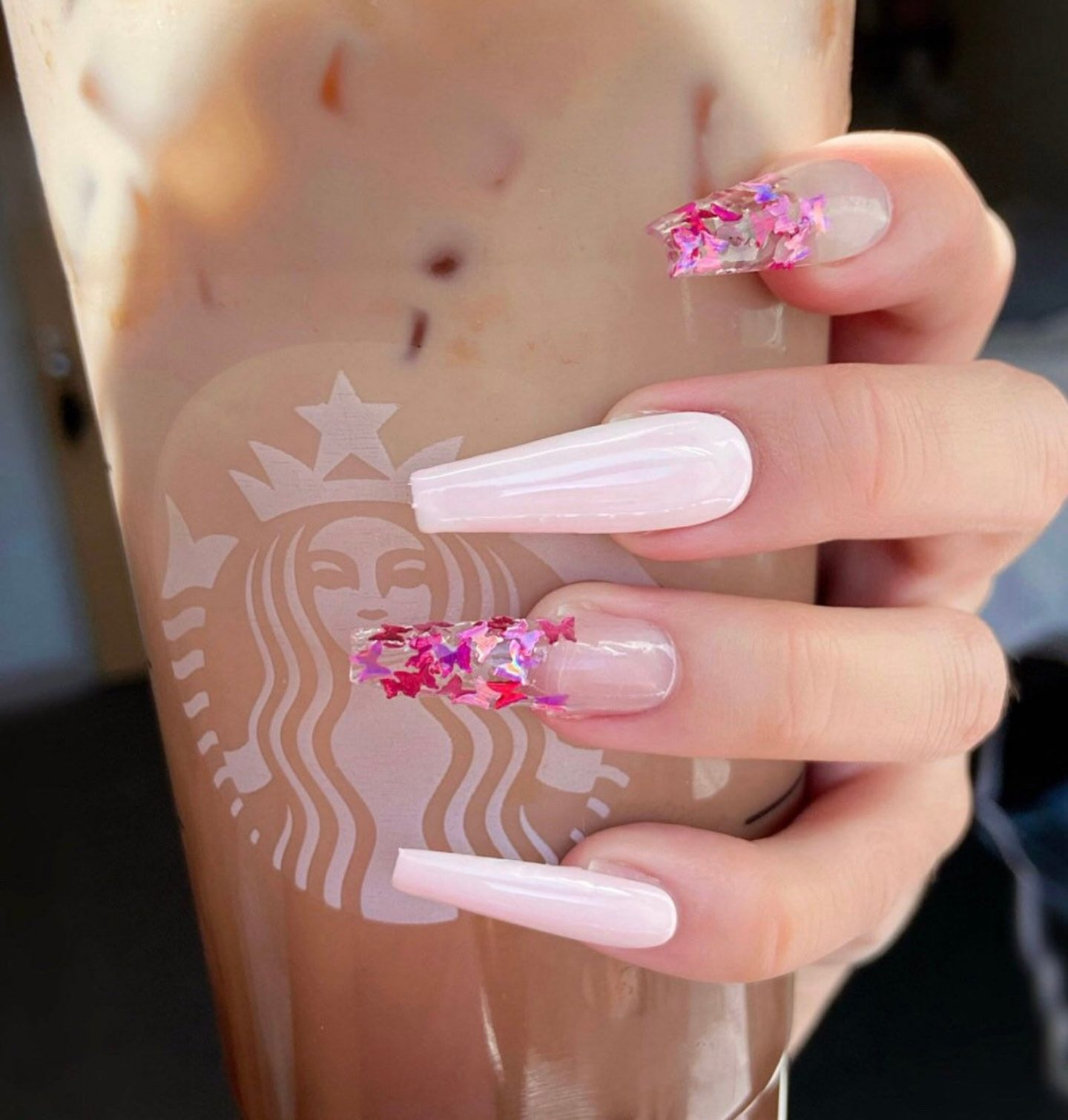 Light pink coffin nails with butterfly nail art
