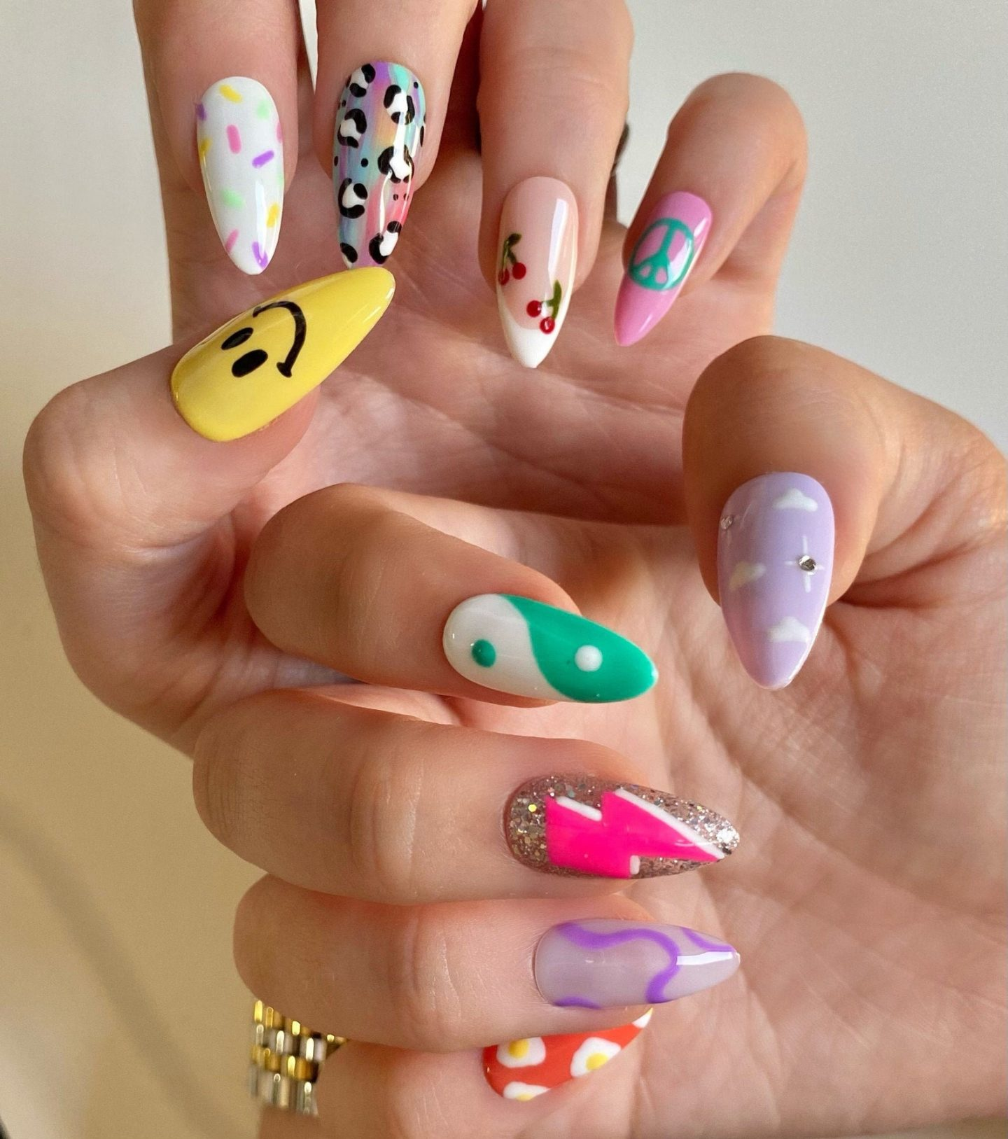 Cute mix and match y2k nails with emojis, yin and yang, and more
