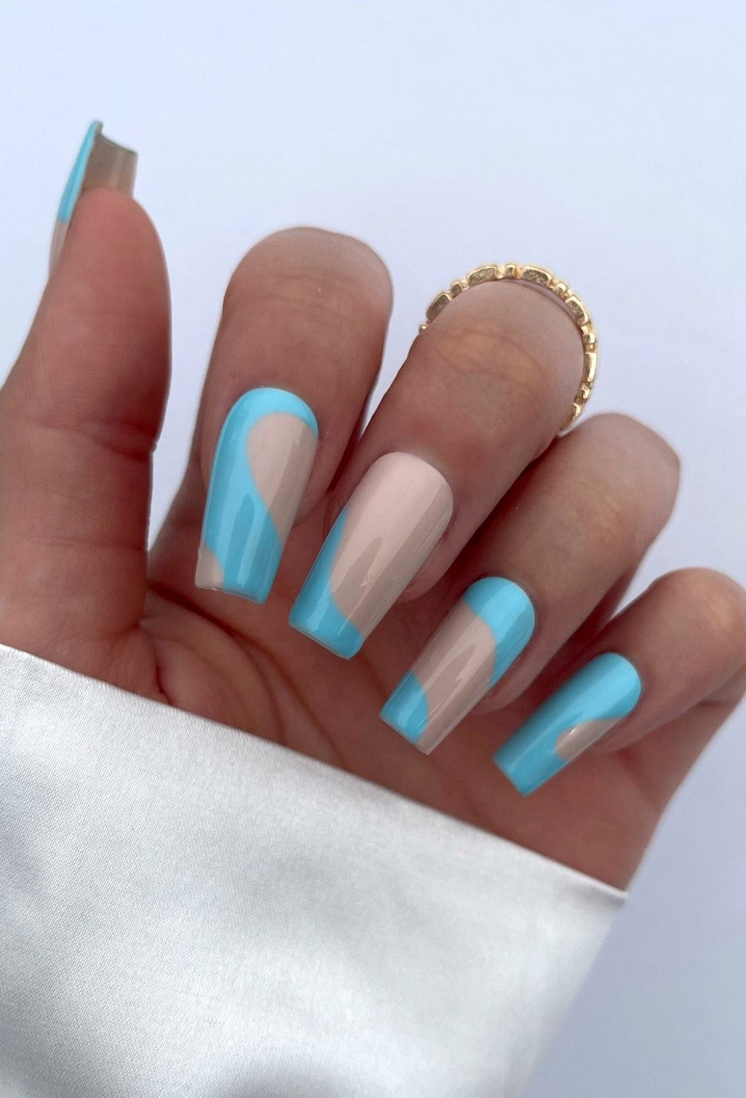 Abstract blue and nude nails with swirls