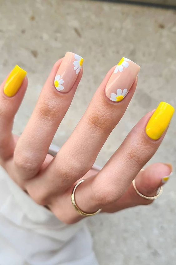 Yellow nails with nude details and daisies