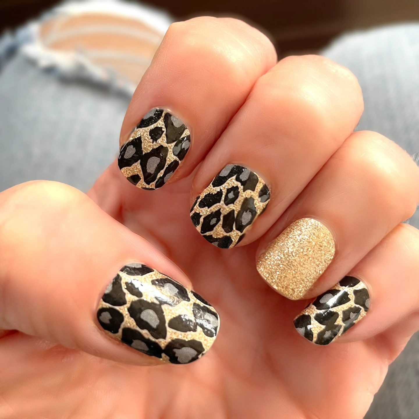 Short black and gold cheetah nails with glitter