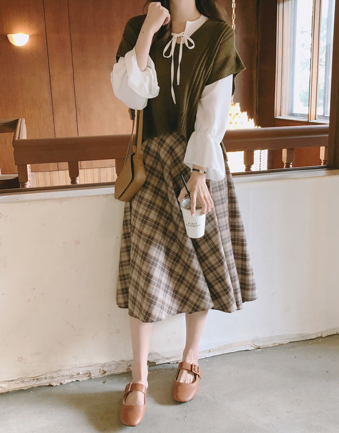 Dark academia outfit with khaki vest and plaid skirt