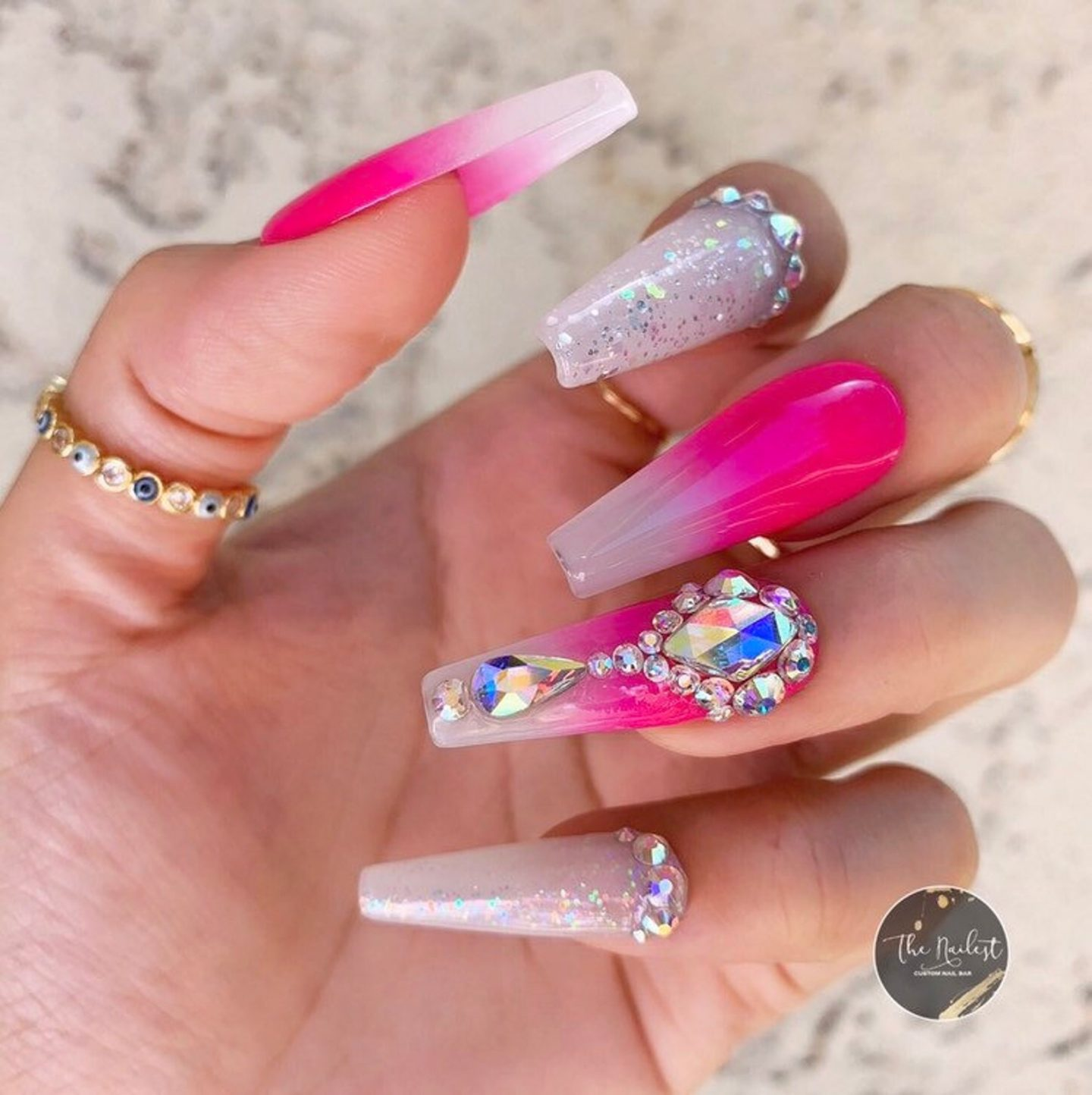 White and hot pink ombre nails with glitter and rhinestones