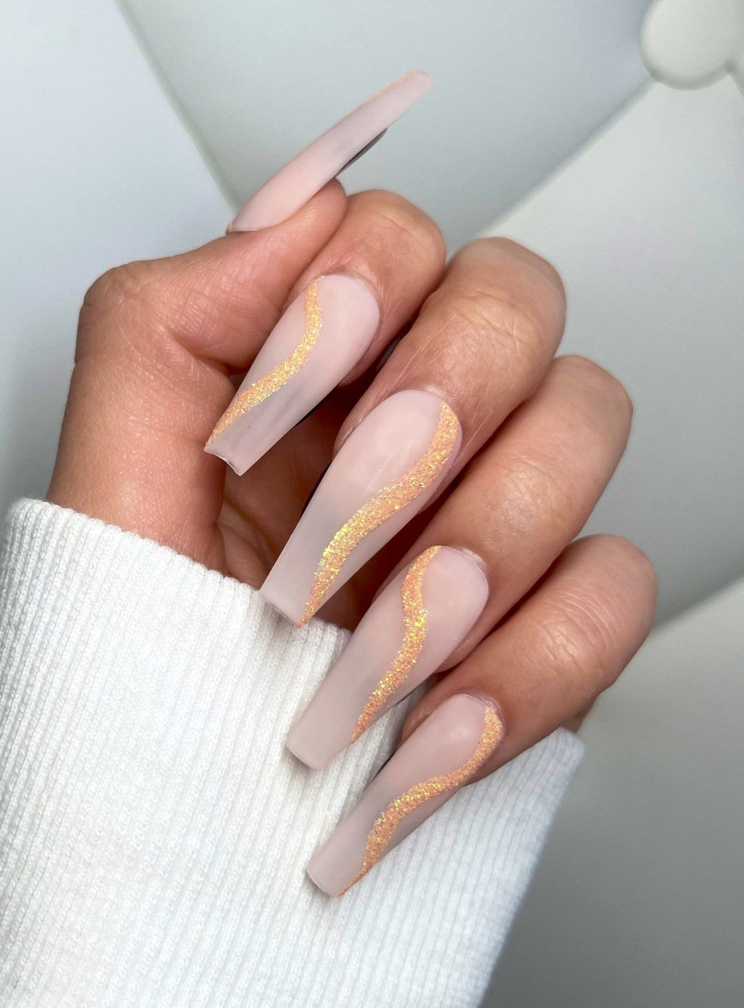 Long abstract nude coffin nails with gold glitter swirls