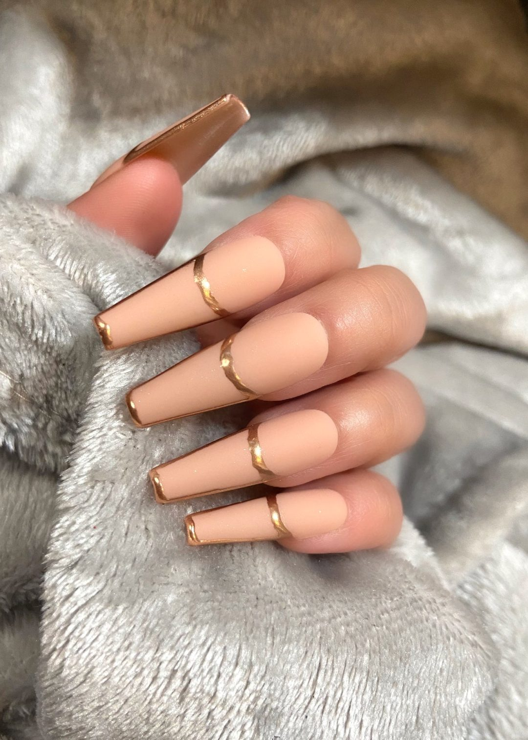 Nude French tip nails with gold lines
