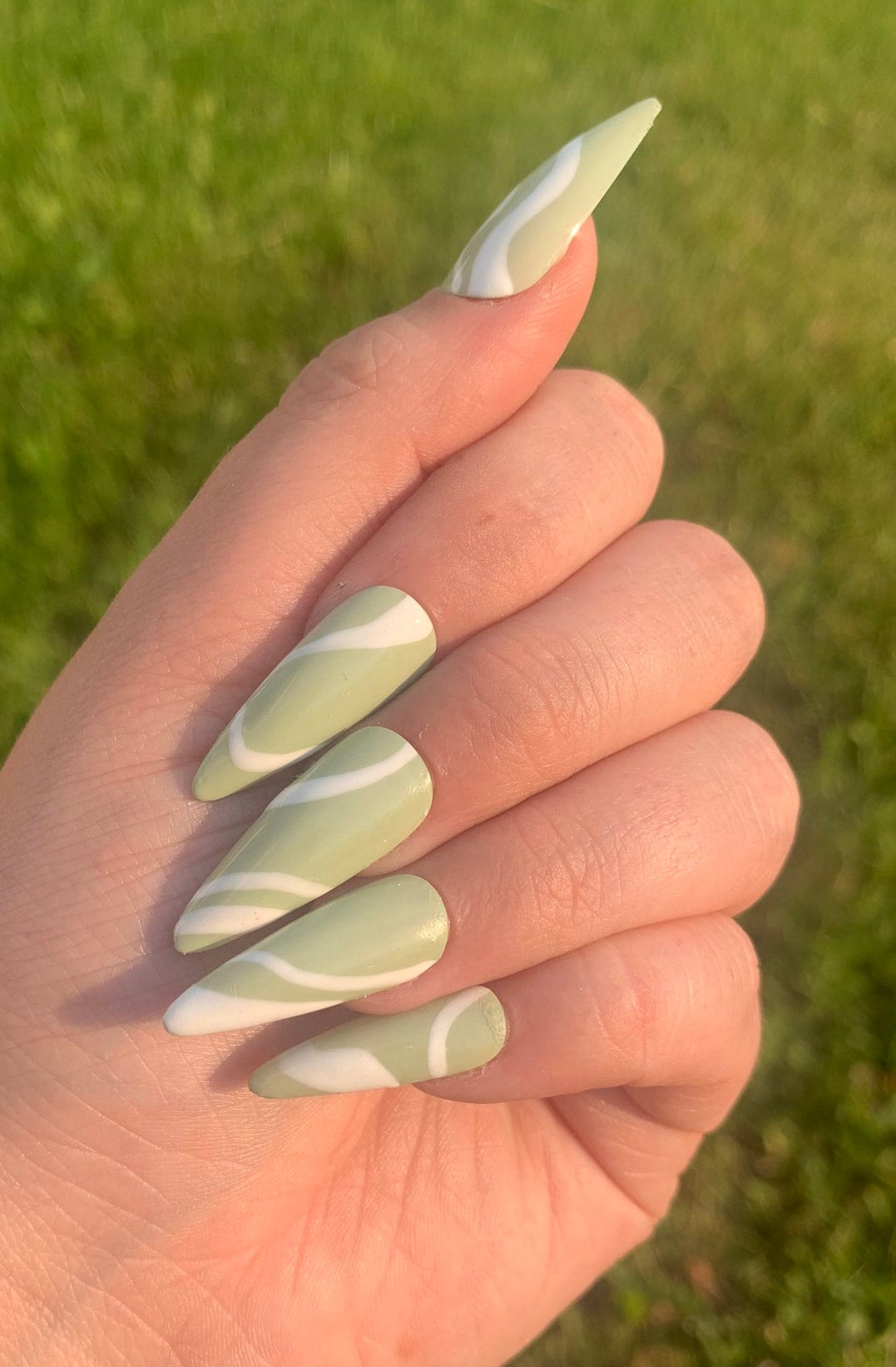 Sage green abstract nails with white swirls