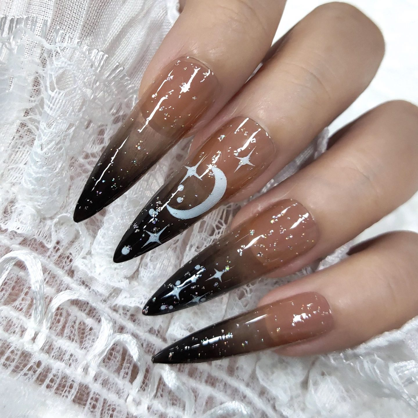 Long black ombre nails with celestial nail art
